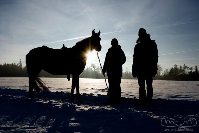 Pferd und zwei Personen im Gegenlicht