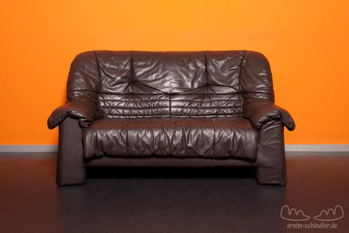 Zweisitzercouch vor oranger Wand