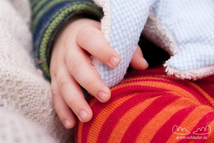Baby greift nach dem Rüssel seines Kuscheltiers